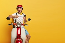 Isolated shot of happy delivery man points at smartphone used for finding route or right address, contacts with customer, poses with rucksack on motorbike, blank copy space on yellow background