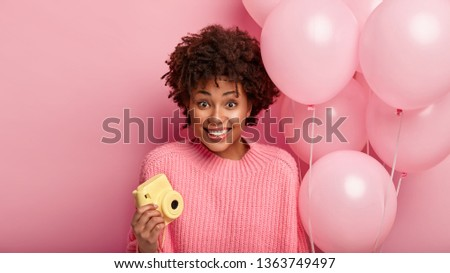 Isolated shot of happy pretty young woman with Afro haircut holds small camera for making pictures, pink balloons, wears casual sweater, smiles positively, comes on birthday party to best friend