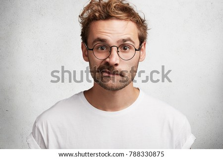 Isolated shot of indignant bearded male curves lips, looks in bewilderment, wears casual t shirt and square spectacles, isolated over white concrete wall. People, facial expressions, reaction concept #788330875