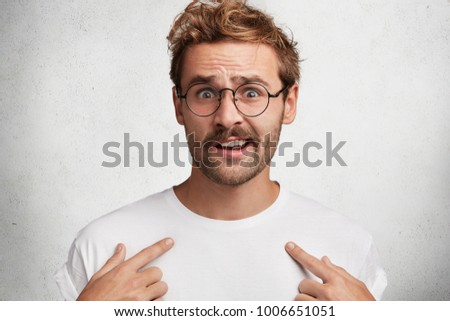 Isolated shot of indignant male with trendy hairstyle indicates at blank copy space of white t shirt, can`t understand something, advertises clothes. People, design, clothing and fashion concept #1006651051