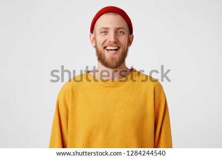 Isolated shot of joyful bearded young cute man laughs joyfully as hears funny joke, wears red hat and sweater, poses against white studio wall. Happiness and positive emotions concept