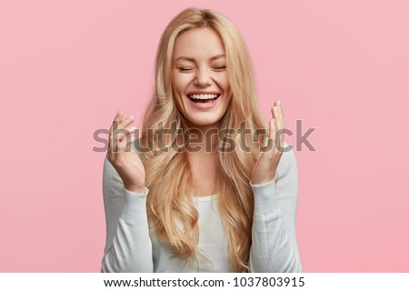 Isolated shot of joyful blonde young cute woman laughs joyfully as hears funny anecdote from friend, has long light hair, poses against pink studio wall. Happiness and positive emotions concept #1037803915
