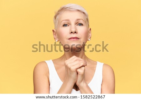 Isolated shot of modern blonde European mature woman in tank top keeping hands under her chin staring at camera with nervous upset look, eyes full of hope, begging, pleading, worrying about something