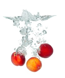 Isolated shot of peach falling into water, isolated on white background
