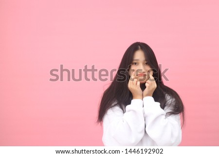 Isolated shot of pretty adult with long hair, broad smile, wears casual outfit, being entertained by friend during party, tilts head and looks with joy, dressed casually, Beautiful Asian models over