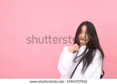 Isolated shot of pretty adult with long hair, broad smile, wears casual outfit, being entertained by friend during party, tilts head and looks with joy, dressed casually, Beautiful Asian models over   #1446192962