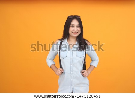 Isolated shot of pretty adult with long hair, wears casual outfit, dressed casually, Beautiful Asian models over  yellow   background for advertising concept