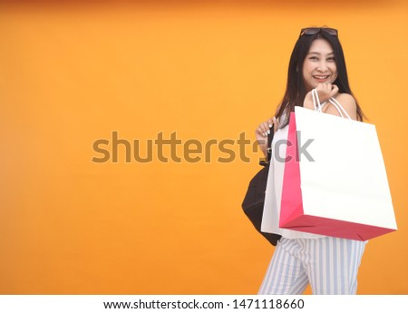 Isolated shot of pretty adult woman with shopping bag, wears casual outfit, dressed casually, Beautiful Asian models over yellow  background for advertising concept