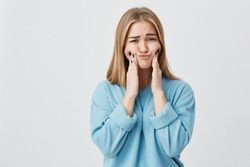 Isolated shot of pretty cute blonde girl in blue clothes touching her cheeks with her hands, showing how big they are. Funny female mocking and posing against studio wall.