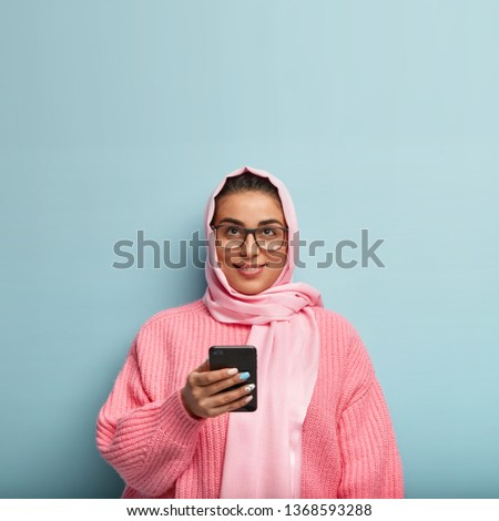 Isolated shot of pretty dreamy Muslim woman uses cell phone for sending messages in social networks, focused upwards, thinks about content of message, stands over blue background. Technology