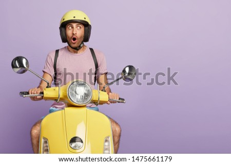 Isolated shot of thoughtful shocked driver drives motorbike, wears protective headgear, forgets about something important, has wonderful trip alone. Emotional motorcyclist poses on his transport