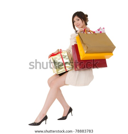 Isolated sitting shopping woman holding bags and gift box, full length portrait on white background.