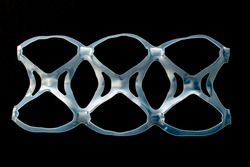 Isolated six pack rings or six pack yokes, connected plastic rings used in multi-packs of beverage on a black background