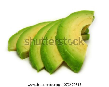 Isolated sliced avocado pieces #1073670815
