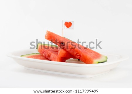 Isolated sliced fresh watermelon on a plate with a cute red heart flag. #1117999499