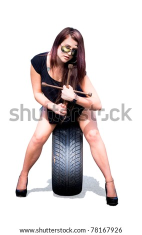 Isolated Studio Photograph Of A Female Mechanic Holding Tools About To Change A Car Tyre Or Tire In A Automotive Mechanic Parts And Service Concept