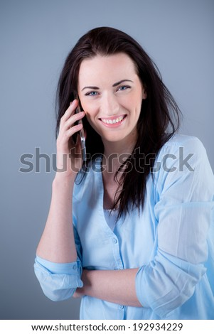 Isolated studio portrait of cheerful young woman on blue background
