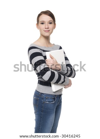 Isolated studio shot of a casually dressed young adult woman holding a laptop computer to her chest and lookign at the camera.