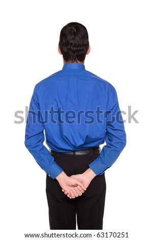 Isolated studio shot of a Caucasian businessman standing with his hands behind his back.