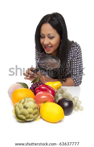 Isolated studio shot of a Latina woman using a magnifying glass to exam fruits and vegetables, deciding what to eat for her healthy diet.