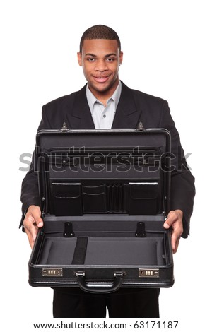 Isolated studio shot of a smiling African American businessman holding an open briefcase as if it contained something valuable.