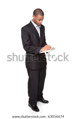 Isolated studio shot of an African American businessman writing on a clipboard.