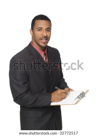 Isolated studio shot of an African American man looking at the camera while smiling and writing on a clipboard he is holding.