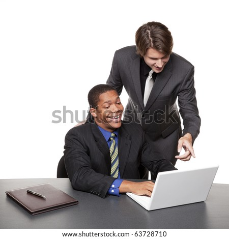 Isolated studio shot of two happy businessmen working on a laptop at a conference table.