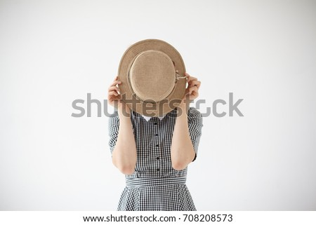 Isolated studio shot of unrecognizable female wearing checkered summer dress covering face with beige round hat posing at white blank wall with copy space for your text or advertising content. #708208573