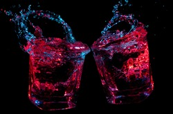 Isolated toasting rocks glasses splashing liquid under colorful glowing lights on a black background