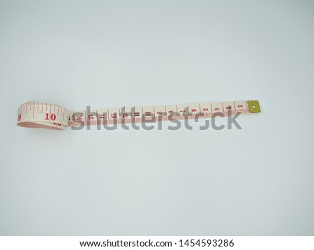 Isolated top shot on the measuring tape that have red centimeters and inches indicator on the white