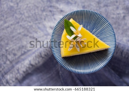 Isolated Top View of Garnished slice of Lemon Cheesecake on blue, round ceramic plate over a purple cloth