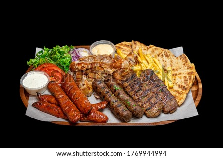 Isolated / Transparent Greek / Arabic Restaurant Grilled Meat Platter, Lamb, Beef, Chicken, Pork Kebab Skewers Sauce Tahini Feta Fries Chips Salad Sausages Foto stock ©