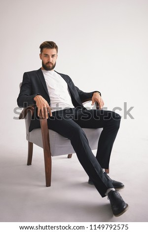 Isolated vertical portrait of successful handsome stylish young European male boss with fuzzy trimmed beard wearing trendy men's wear relaxing in armchair and staring at camera with serious look