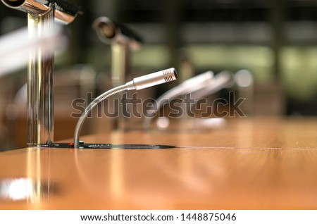 Isolated view of a microphone in the front of a conference room among blurred other mikes in the background - close-up with selective focus and very little depth of field and much copyspace