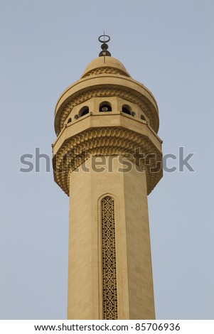 Isolated view of a single minaret against a blue sky