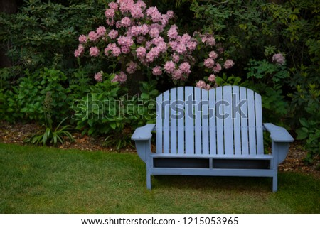 Isolated view of blue wooden adirondack bench in shaded garden setting\n