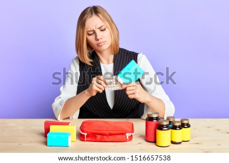 Isolated view of depressed pretty blonde girl taking out blister pack with pills, suffers from strong headache and high temperature, feels unwell, takes medicine by prescription.