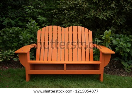 Isolated view of orange wooden adirondack bench in shaded garden setting\n