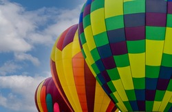 Isolated View of Three Colorful Abstract Patterned Hot Air Balloons against a backdrop of a Blue Sky with White Clouds
