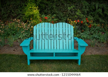 Isolated view of turquoise wooden adirondack bench in shaded garden setting\n