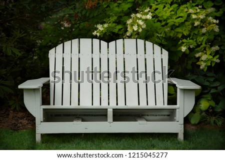 Isolated view of white wooden adirondack bench in shaded garden setting\n