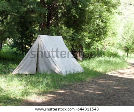 Isolated vintage canvas tent on dirt road. #644311543