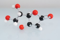 Isolated vitamin C made by molecular model with reflection on white background. Ascorbic acid chemical formula with colored atoms and bonds.
