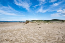 Isolated white beach with grassy sand dunes set against a striated white and blue sky