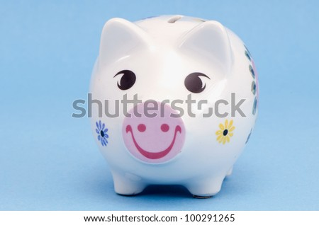 Isolated white ceramic piggy box money-box with smiles and flowers decors on white background. Saving money for black day. Nest-egg.