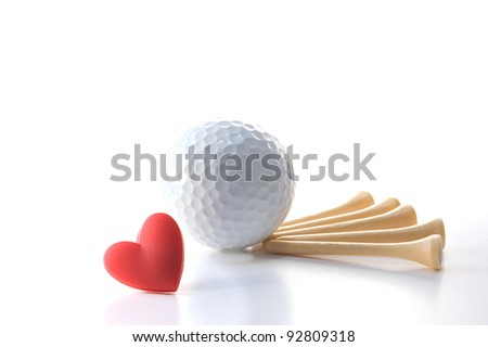 "Isolated white golf ball with wooden tees on white with red heart. Concept Father's Day theme incorporating ""I love golf"" message. Copy space."