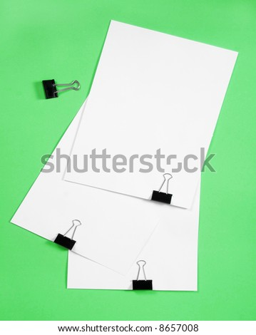 Isolated white paper with  clamp on green background