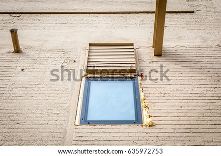 Isolated window on brick wall. Isolated sealed window with caulk on brick face wall. Steel beam and pipe on building exterior facade. Abstract architectural detail and design. Industrial design.