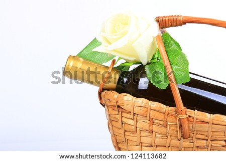 Isolated wine bottle on present basket with white rose